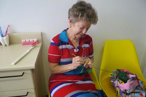 A tranquilidade da avó, fazendo crochê, enquanto a neta era atendida.
